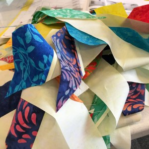 colorful pile of quilting units made with beautiful island batik fabrics