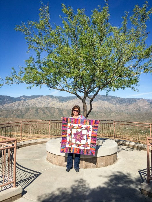 Karen Overton holding her quilt Illuminated Journey outside near a breathtaking view of Arizona