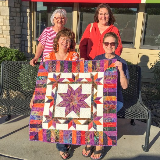 four quilting friends holding a colorful quilt