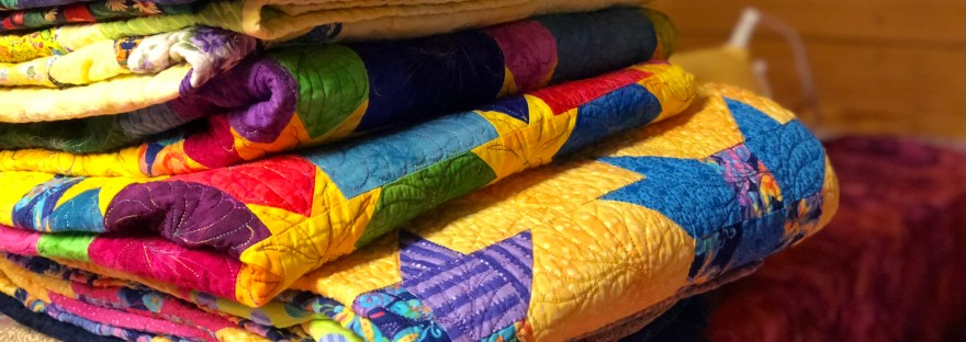 colorful stack of quilts by The Quilt Rambler