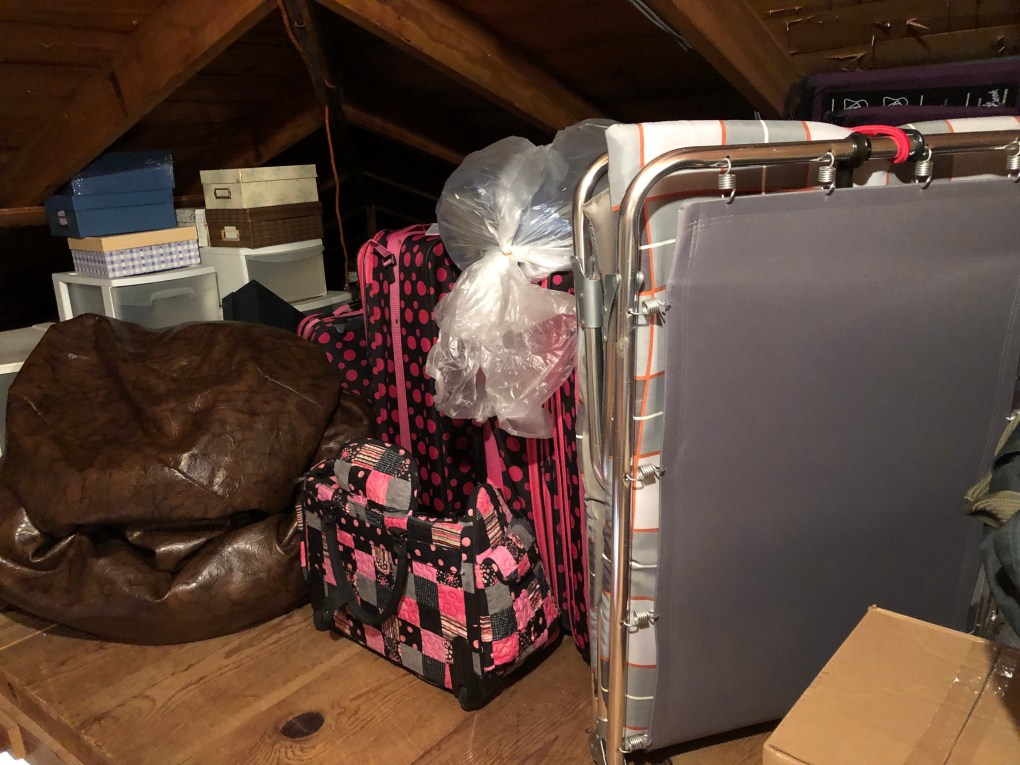 luggage, a cot, bean bag and storage boxes in an attic