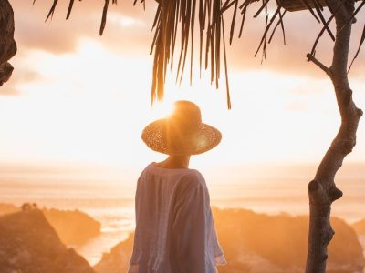 unrecognizable woman enjoying sunset over sea