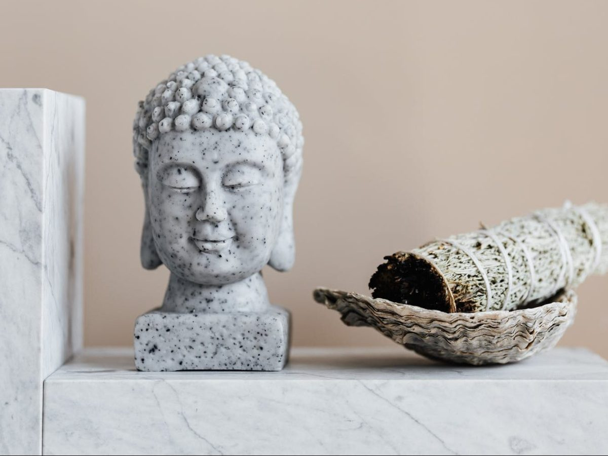 stone buddha and sage incense bundle in bowl on marble shelf