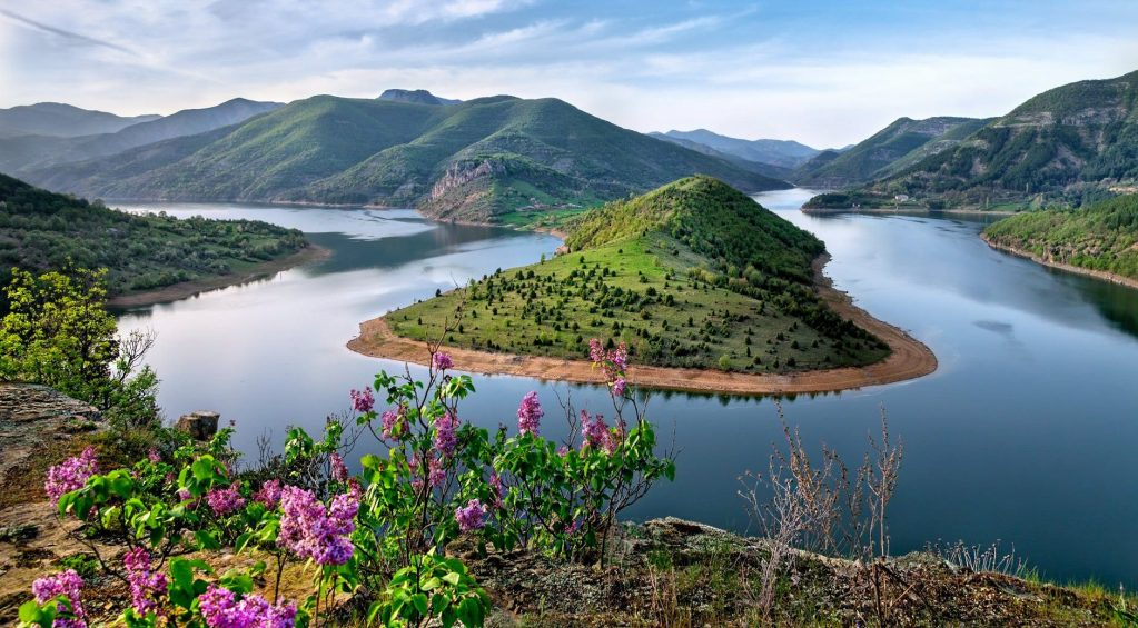 green mountain surrounded by body of water photo