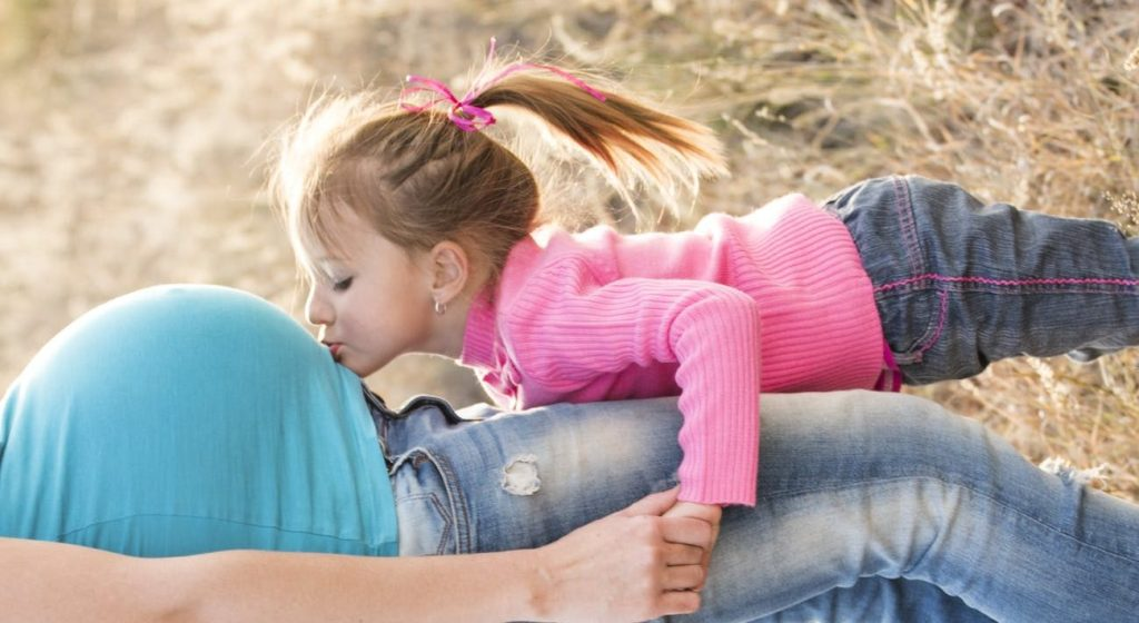 girl in pink sweater and grey jeans kissing tummy of pregnant woman in blue shirt and blue denim jeans