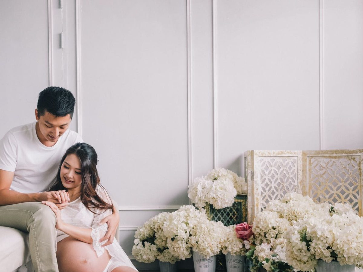 smiling pregnant couple sitting in living room with flowers