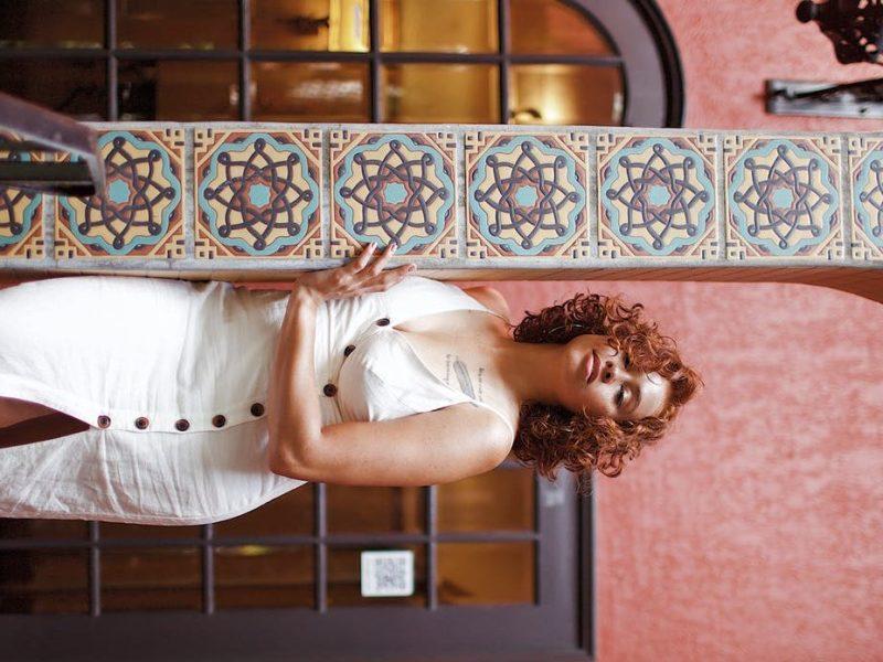 woman leaning on pillar