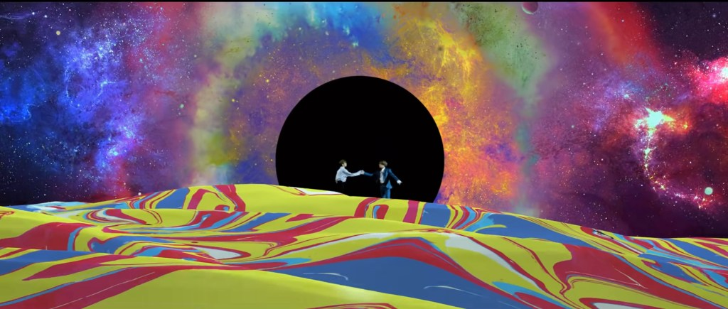 Two figures grasp hands on a colorful surface, with a black hole and galaxies behind them