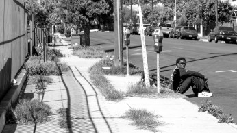 A man, Louis, rests on a curb alongside his bike.