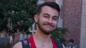 A USC student smiles, noticing a stranger taking a candid photo.