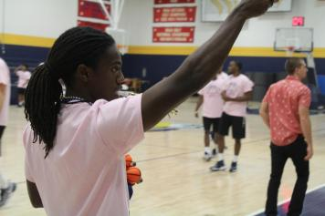 Junior Anthony Harper II, a member of Ram Squad, throws prizes to the crowd at Midnight Madness. Photo by Hannah Onder