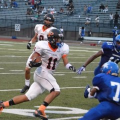 Felix Manus-Schell (#11) carries the ball past two Perry players.