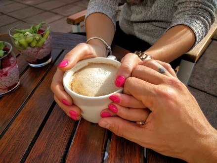 Couple holding hands over mug of coffee. This signifies a couples workshop helping couples during COVID.