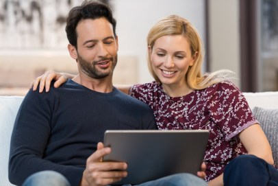 Happy couple looking at ipad. This signifies relationship and marriage help during COVID with online hold me tight relationship enhancement workshop for couples.