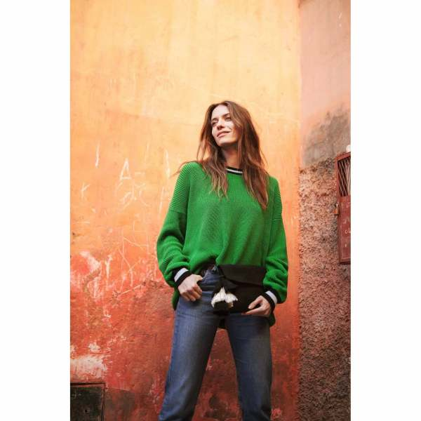 model with a green pullover wearing Black Cotton Clutch with Black and White Tassel