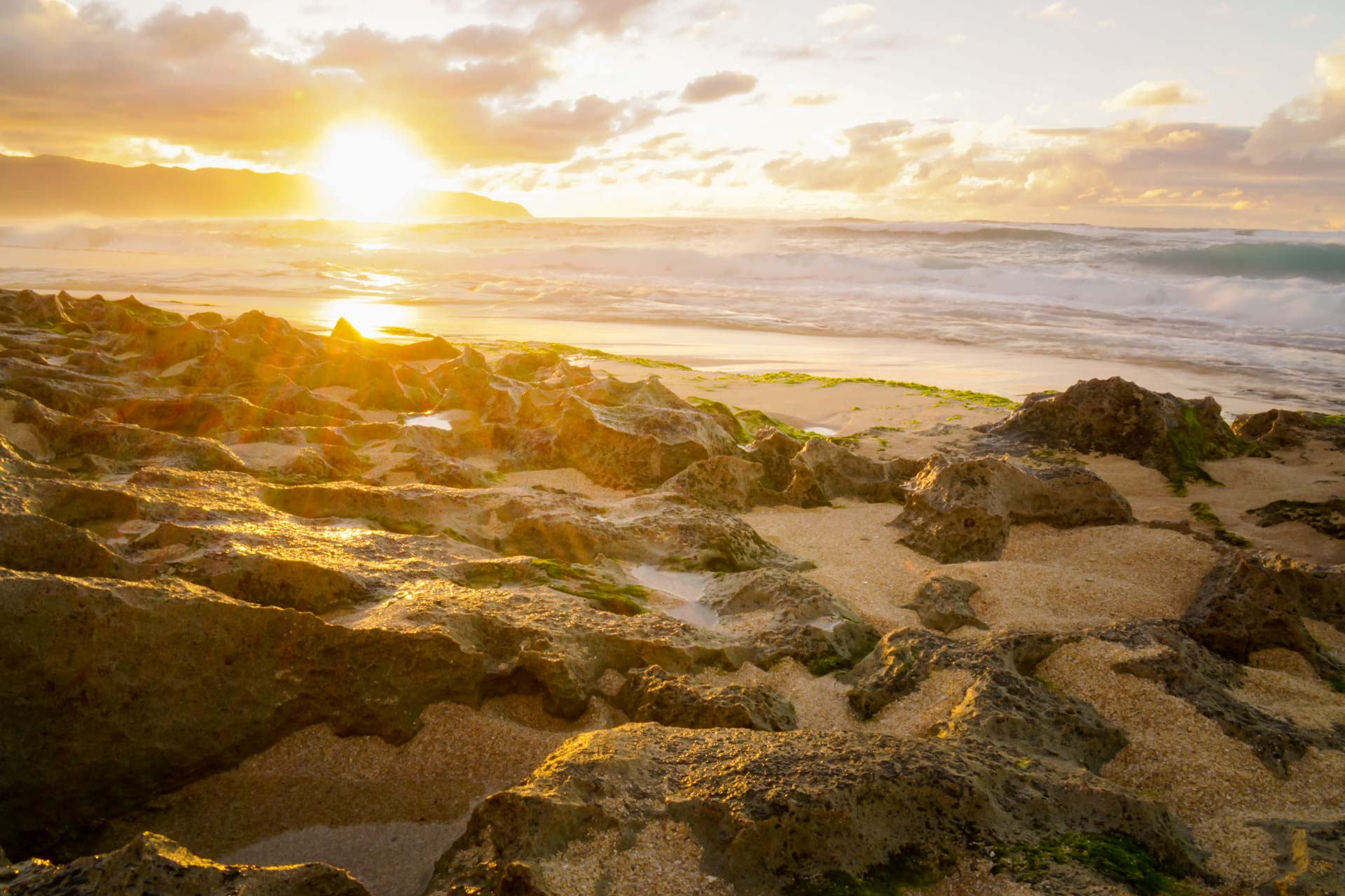 thereafterish feature photo of north shore sunset with clouds and seaweed covered reef