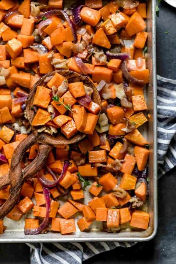 overhead view of a wooden spoonful of Roasted Sweet Potatoes with Maple and Bacon resting on a sheet pan of them