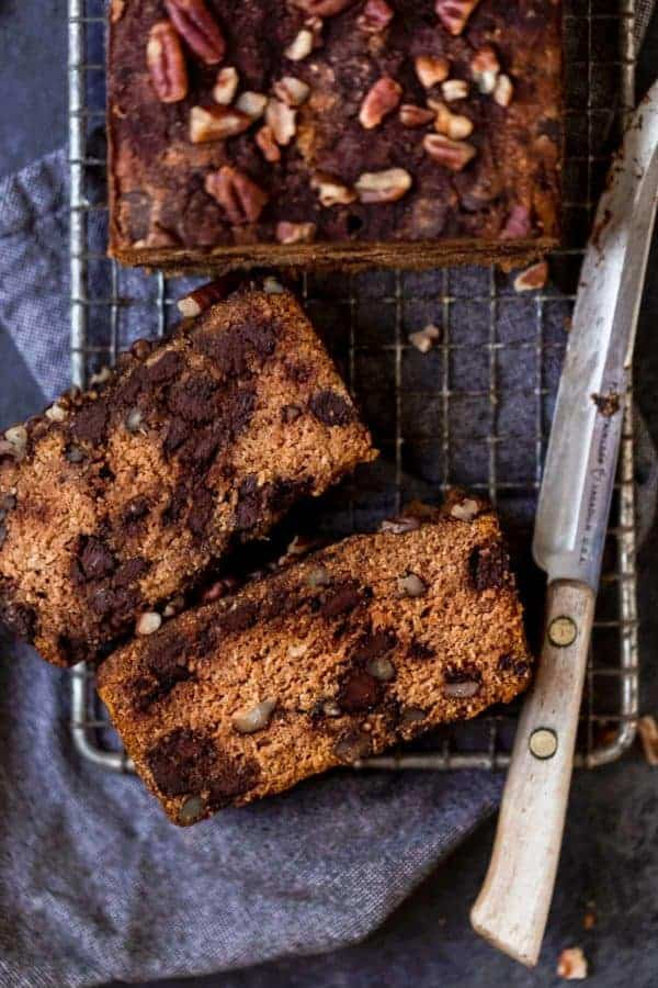 Two slices of healthy paleo pumpkin bread with chocolate chips on on a wire cooling rack.