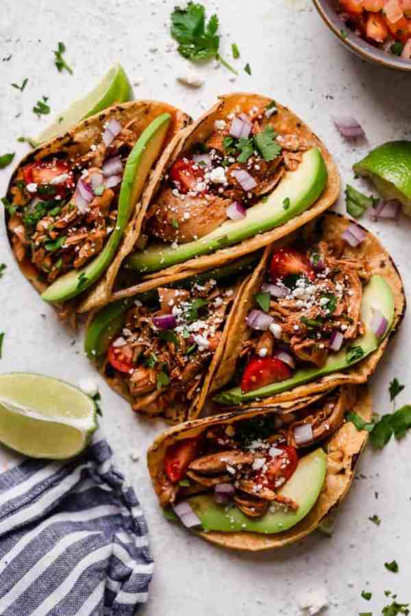 Four Slow Cooker Chicken Tacos in a corn tortilla with fixings.
