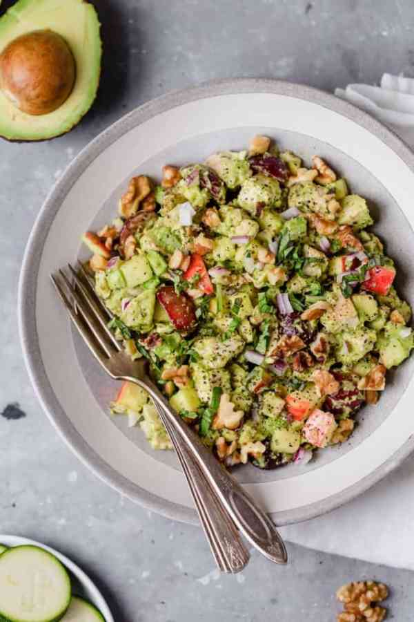 Avocado chicken salad served on plate with utensils resting in it with walnut garnish. Half an avocado as an accent.