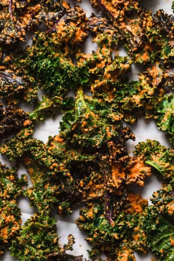 Overhead photo of the sauce coated Cheese Pizza Kale Chips on a baking sheet, ready for the oven.