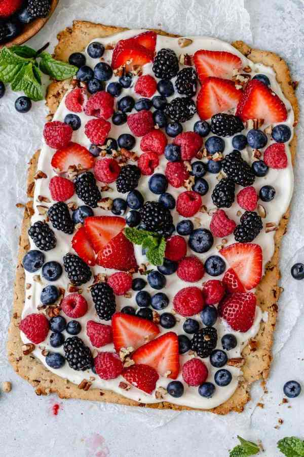 Overhead photo of Gluten-free Berry Fruit Pizza garnished with a spring of mint in the center. Pizza is topped with an assortment of berry, chopped pecans and a sprig of mint leaves.