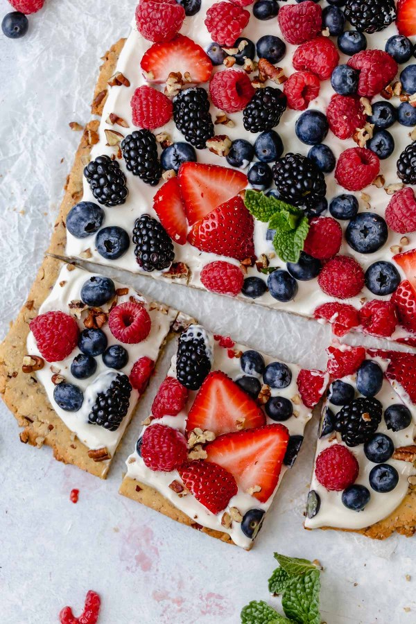 Overhead photo of Gluten-free Berry Fruit Pizza garnished with a sprig of mint in the center.