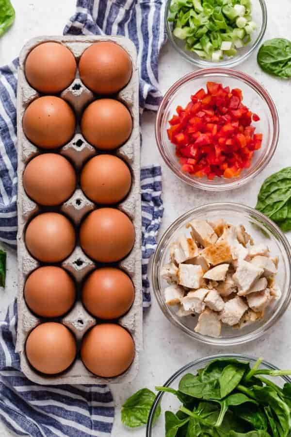 Overhead shot of ingredients for the Buffalo Chicken Egg Muffins including brown eggs, green onion, diced red pepper, diced chicken and spinach.