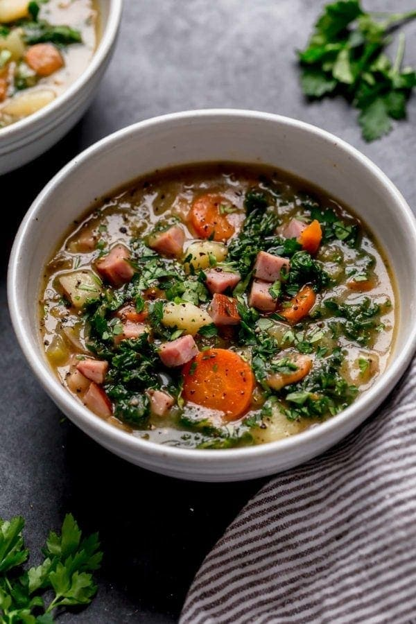 Creamy ham and potato soup with carrots and kale in a cream speckled bowl