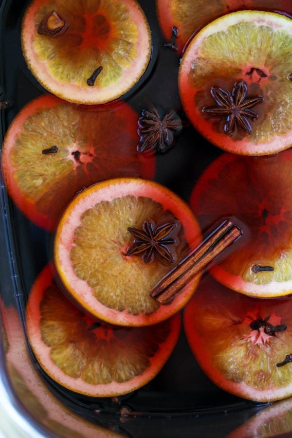 mulled wine in a crockpot with orange, cinnamon and star anise