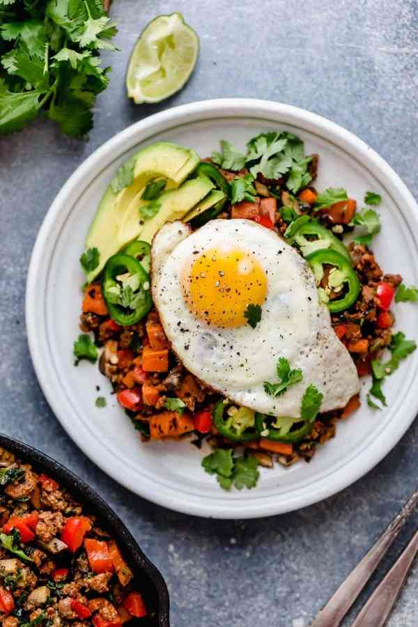 Tex-Mex Sweet Potato Hash served on a white plate with a fried-egg on top.
