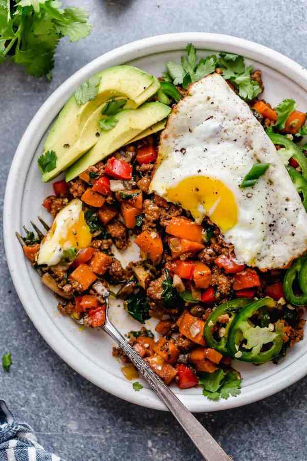 Tex-Mex Sweet Potato Hash served on a white plate with fork and a fried-egg on top with avocado slices, jalapeño slices and cilantro.