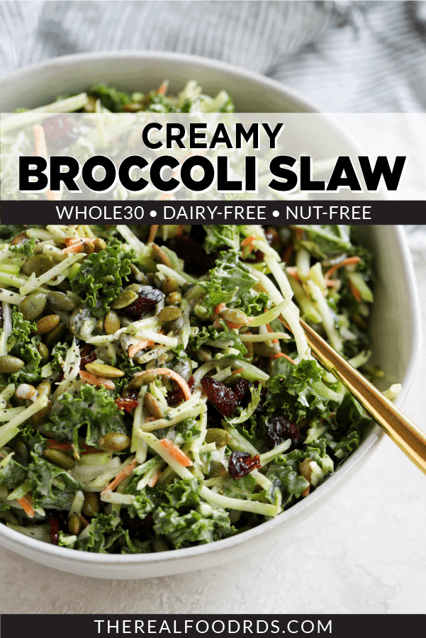Broccoli Slaw made with homemade dressing and dried cranberries in a white bowl with gold serving spoon.