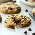 A peanut butter oatmeal cookie broken in half to show the soft and chewy texture