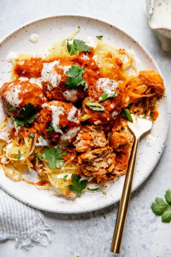 Buffalo Chicken Meatballs served over spaghetti squash, topped with a drizzle of ranch and garnished with cilantro and green onion. Served on a white plate.