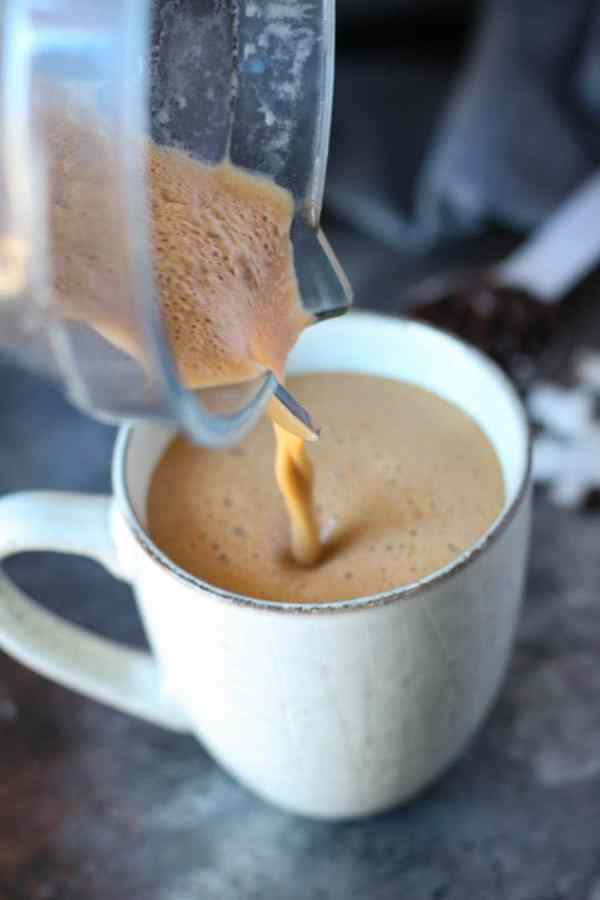 Cinnamon coconut latte being poured out of a blender into a coffee cup.