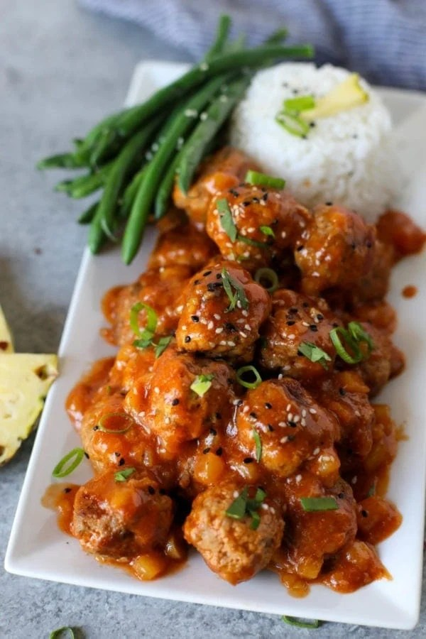 A pile of Sweet and SourA pile of Sweet and Sour Meatballs on a long white tray with steamed rice and green beans.