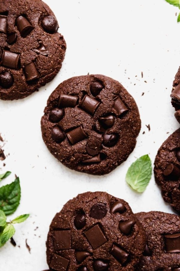 Overhead view of Low Sugar Double Chocolate Mint Cookies on a white surface that are studded with chocolate chips and chunks.