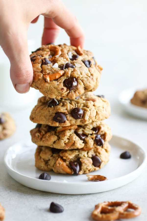 A stack of Peanut Butter Chocolate Chip Pretzel Cookies with a hand grabbing the top cookie.