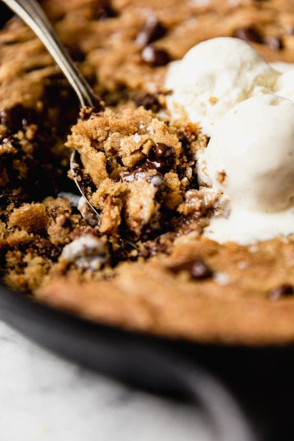 The perfect bite... a big spoonful of vegan chocolate chip cookie skillet warm from the oven and topped with slightly melted vanilla ice cream