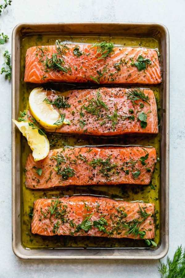 Four salmon fillets for the Mediterranean bowl. The salmon fillets are on a sheet pan marinating in a lemon-herb marinade and topped with fresh herbs and a couple lemon wedges.