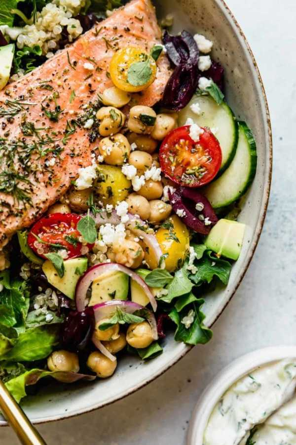 Mediterranean Bowl with Salmon in a light colored bowl with a gold fork.