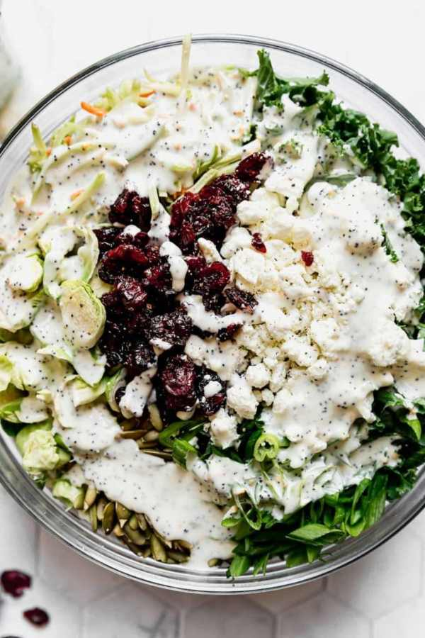 Sweet Kale Salad ingredients in a large clear bowl before being tossed together.