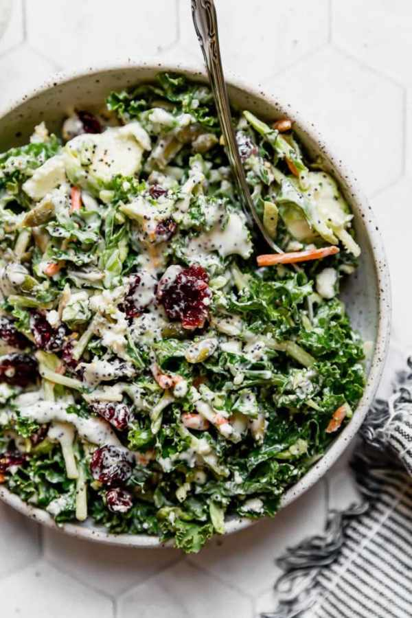 Sweet Kale Salad in a white speckled bowl with a serving spoon in it.
