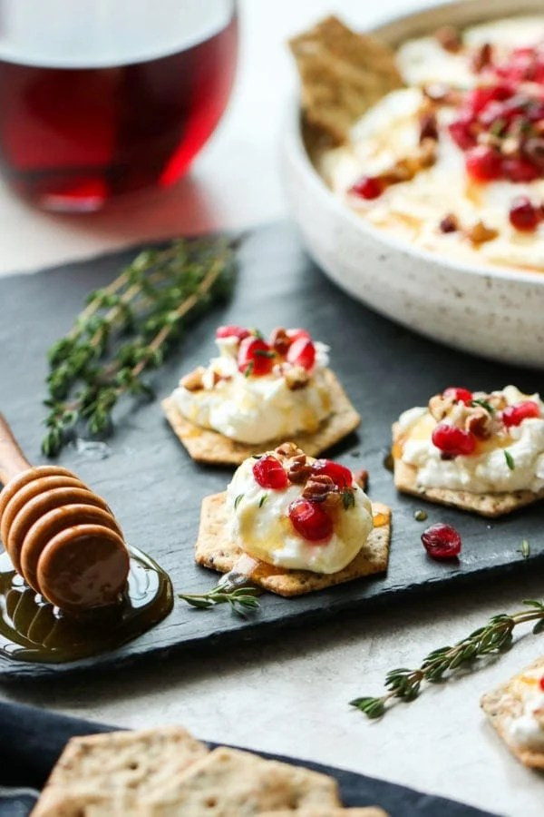 Honey Whipped Goat Cheese with Pomegranate served on top of crackers.