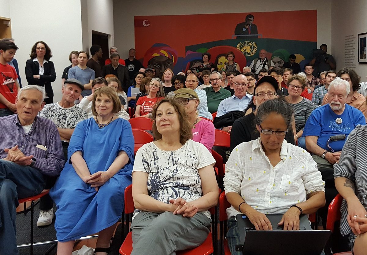 Embassy protectors pack the Hugo Chavez library for an event with John Kiriakou. By Margaret Flowers.