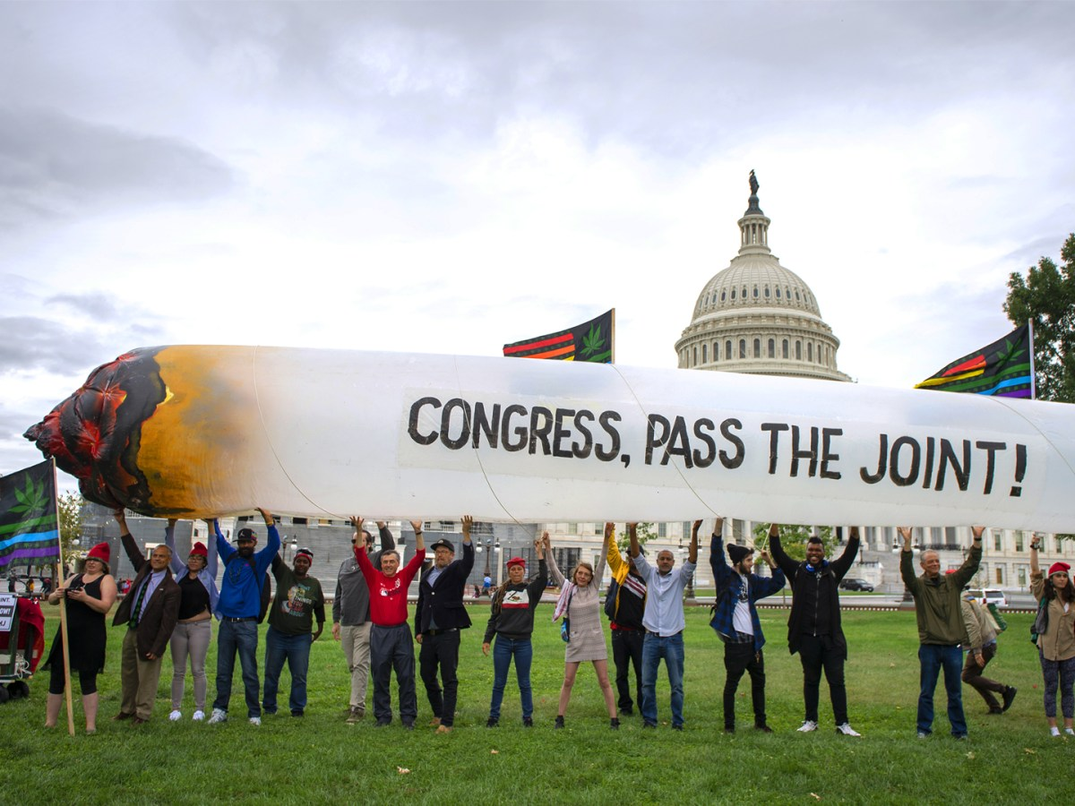 Marijuana activists hold up a 51-foot inflatable joint