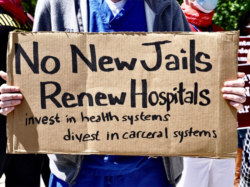A health worker holds a sign during a nurses protest at Rikers Island Prison over conditions and coronavirus threat on May 7, 2020 in New York City