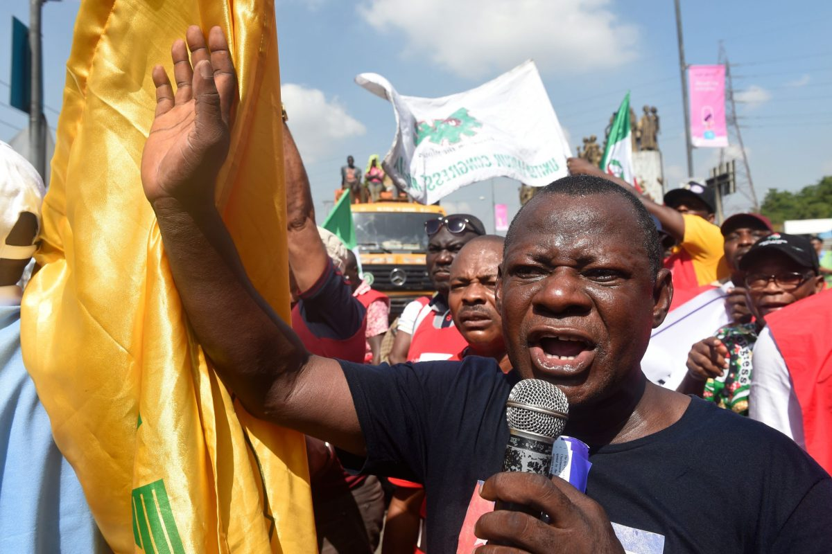 Abiodun Aremu speaks into a microphone as he takes part in a protest