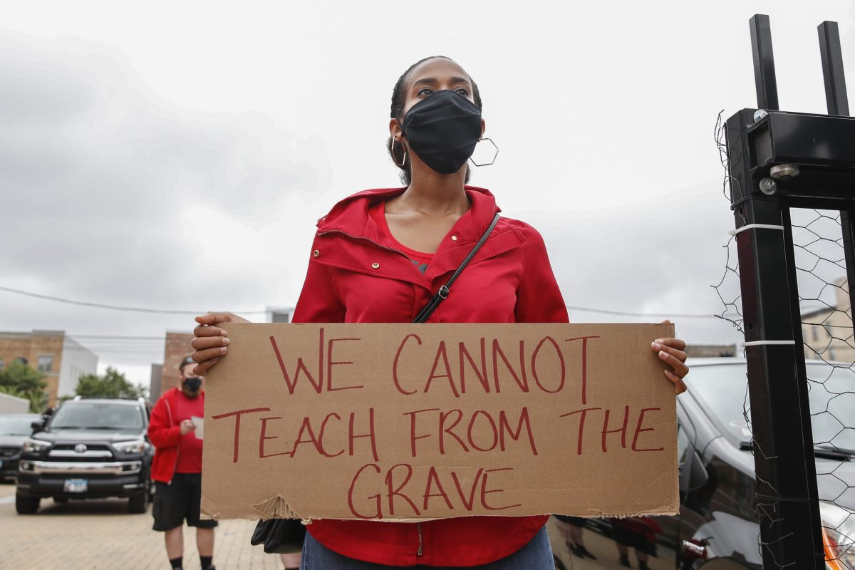 "A teacher at a Chicago Teachers Union protest holds a sign reading ""We cannot teach from the grave."""